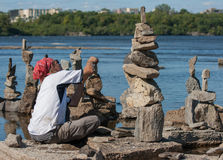 Man Stone Balancing. OTTAWA, CANADA - AUGUST 18: Dan Davis of Canada balances stones while participating in the  International Stone Balance Festival on August Stock Photos
