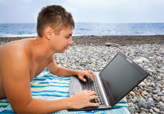 Man on stony beach, looking in laptop screen Stock Photos