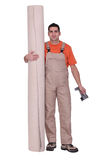 Man stood with carpet roll. Man stood with a carpet roll Royalty Free Stock Photo