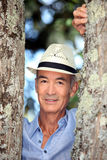 Man stood between two trees. Man wearing hat stood between two trees Royalty Free Stock Photo