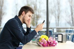 Man stood up in a date checking phone messages Royalty Free Stock Photography