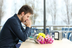 Man stood up in a date by his girlfriend. Sad man with bunch of flowers stood up in a date by his girlfriend in a coffee shop royalty free stock image