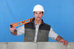 Man stood by wall. With spirit-level Royalty Free Stock Photos