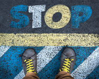 Man on stop sign. Word Stop written on an asphalt road with legs and shoes Stock Photos
