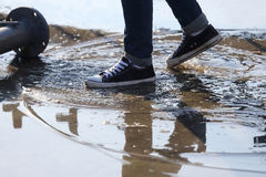 Man stops with his foot in a puddle. The man stops with his foot in a puddle Royalty Free Stock Images