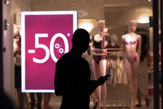 Man at a storefront with discounts. Man stands and looks at the store window of a woman`s underwear, in the window hangs advertising discounts royalty free stock image