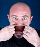 Man sträckning av hans mun för att göra en rolig framsida Royaltyfri Fotografi