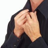 Man straighten collar of his black shirt closeup Stock Photos