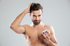 Man straighten hair and holding cream isolated Stock Images