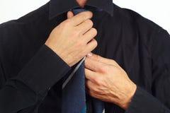 Man straighten his tie over black shirt closeup Royalty Free Stock Photography
