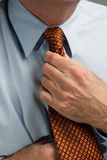 Man straightening necktie Royalty Free Stock Image