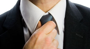 Man straightening tie. A businessman in the act of straightening/loosening his tie Stock Photography