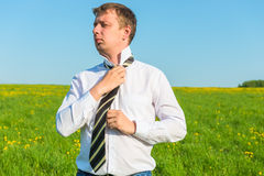 Man straightens his tie Stock Images