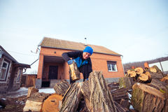 Man with a strained face pulls out a log from the wood pile Stock Images