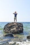 Man stranded on a rock in ocean. Calling for help stock image