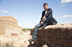 Man on straw bale. Young man looking in the distance on top of a straw bale Stock Photo