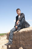 Man on straw bale. Young man looking in the distance Stock Image