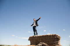 Man on straw bale. Young man think like he fly on top of a straw bale Stock Images
