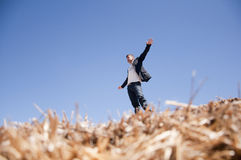 Man on straw bale. Young man think like he fly on top of a straw bale, view from down Stock Photo