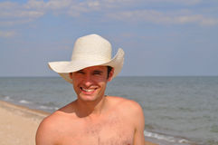 A man in a straw hat on the beach Stock Image