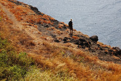 Man in Straw Hat Hiking at Cliff Edge Stock Photography