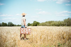 Man in straw hat holding old suitcase in wheat Royalty Free Stock Photo