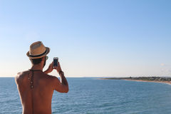 Man with a straw hat making a photo. Man with a straw hat and a collar shooting a photography to the sea with a smartphone Royalty Free Stock Photography