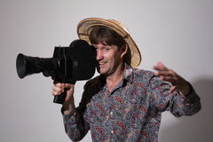 A man in a straw hat with an old movie camera on a gray backgrou Stock Image