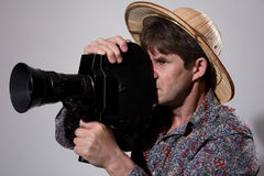 A man in a straw hat with an old movie camera on a gray backgrou Royalty Free Stock Image