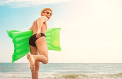 Man in straw hat runs with air swimimg mattress in the sea Royalty Free Stock Photos