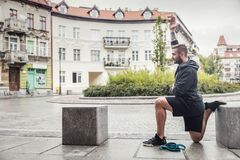 Man streching his legs in the city. Millenial slim man streching his body in a city site. After-training routine Stock Photography