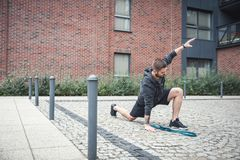 Streching. Urban outdoor activities. Man streching in an urban scenery, representing healthy habits of millenial generation Royalty Free Stock Photo