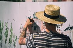 Man street artist at work painting royalty free stock photography