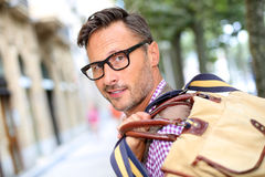 Man in street holding bag on shoulders Royalty Free Stock Images