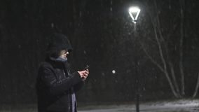 The man in the street light. The guy looks into his smartphone. It`s snowing against the background of lamp. Slow motion