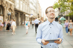 Man on street looking up, hold tablet in hands Stock Photos
