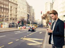Man on the street with mobile phone Stock Images