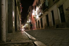 Man on a street in night. Man walking on a cobblestone street in night in Old Lisbon, Portugal Royalty Free Stock Photography