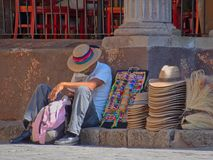Man in street sitting on sidewalk selling hand-crafted hats and bracelets in San Miguel de Allende stock photography