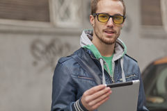 Man On Street Use Ipad Tablet Computer. Young man with yellow glasses use iPad tablet computer on street, public space. Blurred background Royalty Free Stock Photography