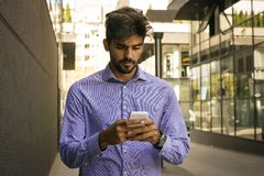 Man on street and using mobile phone. stock photography