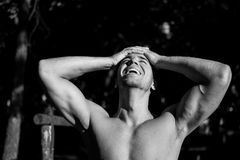 Man street workout. Male working out in the forest early in the morning. He was taking a brake with his hands on the head and smile on his face stock image
