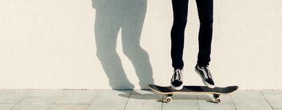 Man On Street. Young man jumping on the skateboard on city street Stock Image