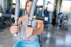 Man strength training on fitness machine at gym. Gym machine closeup on male hands. Male athlete training chest muscles on fitness equipment pec deck fly working stock photo