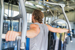 Man strength training hard at fitness gym center. Man from behind training at fitness gym. Man doing workout on fitness machine at gym. Gym trainer athlete stock image