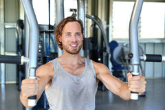 Man strength training hard at fitness gym center. Man training hard at fitness gym. Man doing workout on fitness machine at gym. Gym trainer athlete working out royalty free stock image