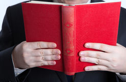 Man in stress holding an open red book Stock Photos
