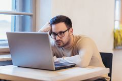 Man stressed while working on laptop. Upset disappointed young businessman sitting at workplace with hands on head Royalty Free Stock Photography