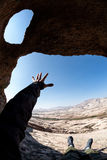 Man stretch his hand in the desert cave Royalty Free Stock Image