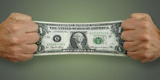Man stretches a $1 dollar bill Stock Image